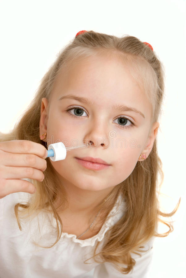 Little girl takes nose drops. On white background stock image