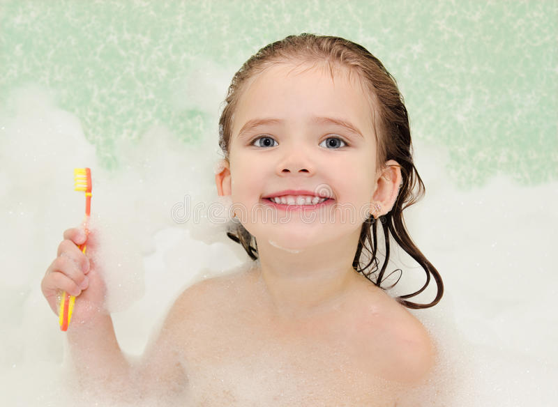 Little girl is taking a bath holding toothbrush stock photo