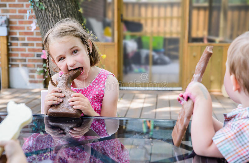 Little Girl Taking a Bite Out of a Chocolate Bunny. A little girl in a pink dress sits outside taking a big bite out of a large chocolate bunny on Easter day stock image