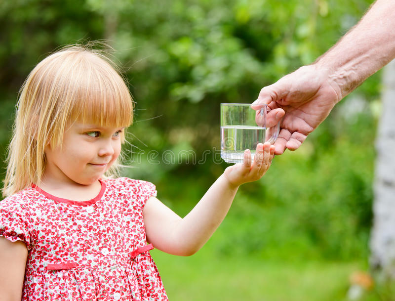 Little girl with taking glass of water stock photos