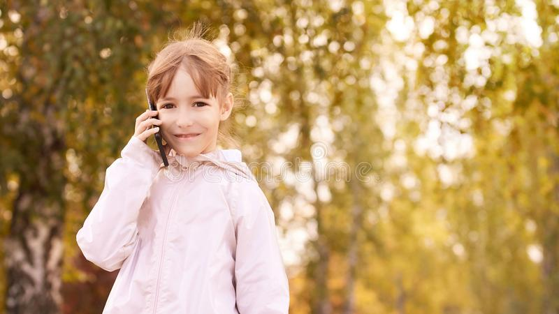 Little girl talk phone. Autumn background royalty free stock photo
