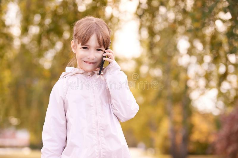 Little girl talk phone. Autumn background royalty free stock photos