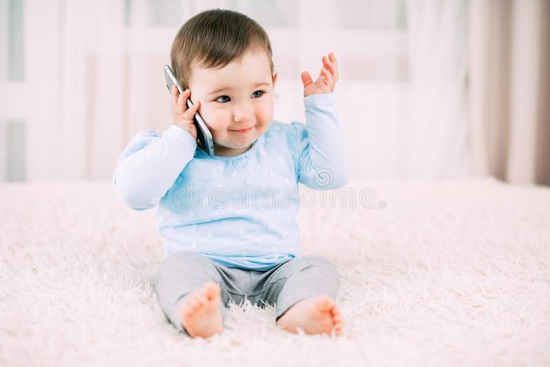 A little girl talking on a smartphone smiling and happy royalty free stock photos