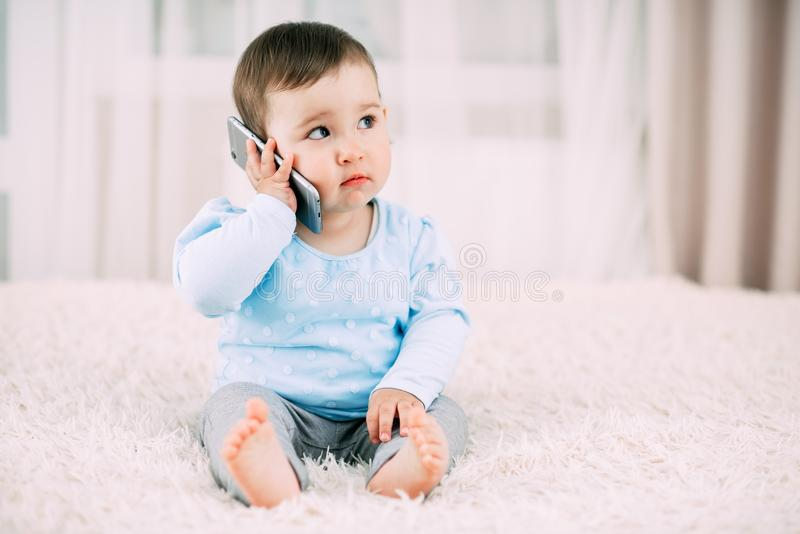 A little girl talking on a smartphone smiling and happy royalty free stock photography