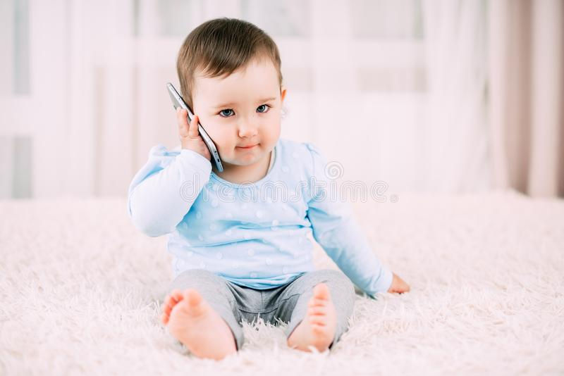 A little girl talking on a smartphone smiling and happy royalty free stock images