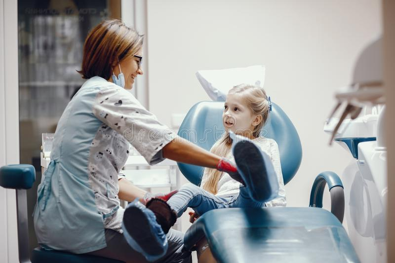 Cute little girl sitting in the dentist`s office. Little girl talking to the dendist. Child in the dentist`s office. Woman in a uniform stock photography