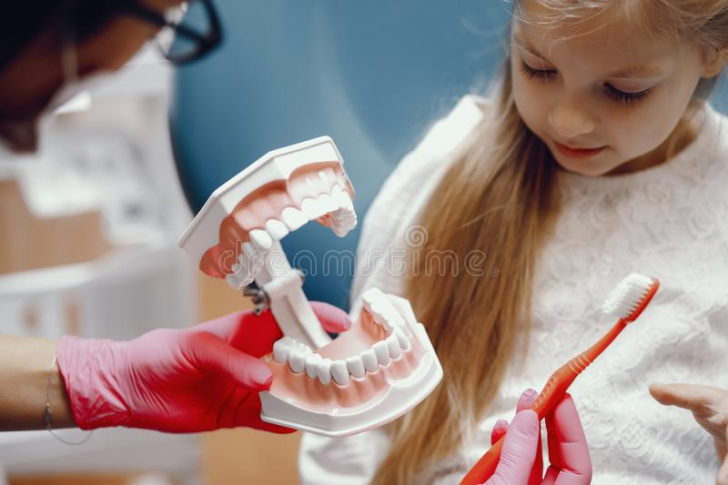 Cute little girl sitting in the dentist`s office. Little girl talking to the dendist. Child in the dentist`s office. Woman in a uniform royalty free stock photo
