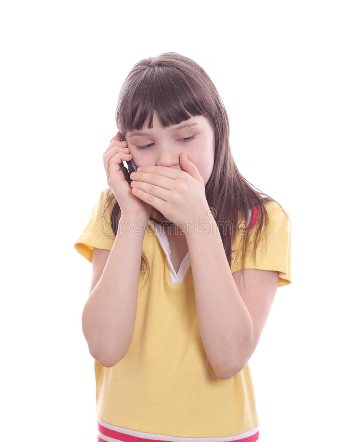 The little girl talks by a mobile phone. Isolated object stock photo