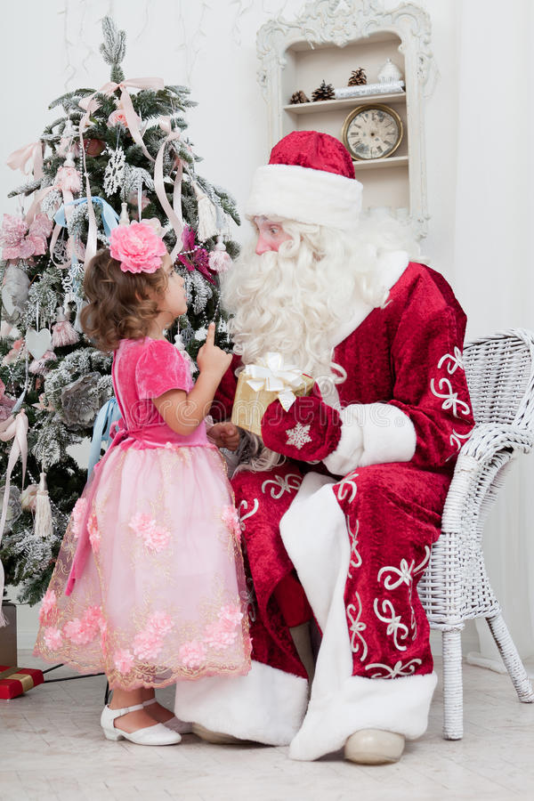 Little girl talks to Santa Claus. Near a Christmas fir-tree stock photography