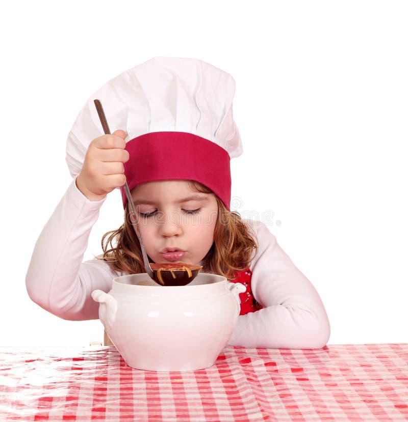 Little girl taste soup. Little girl cook taste soup royalty free stock photos