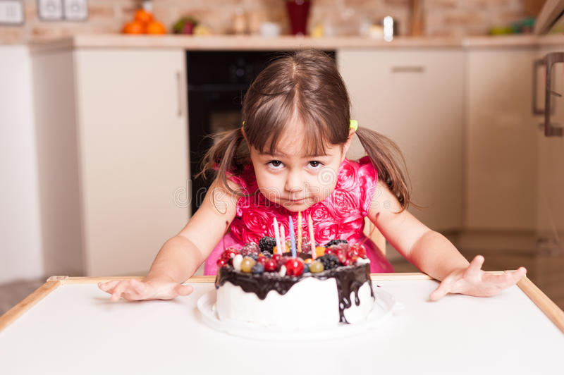 Little girl with tasty cake. Little girl with hat and cake stock photo