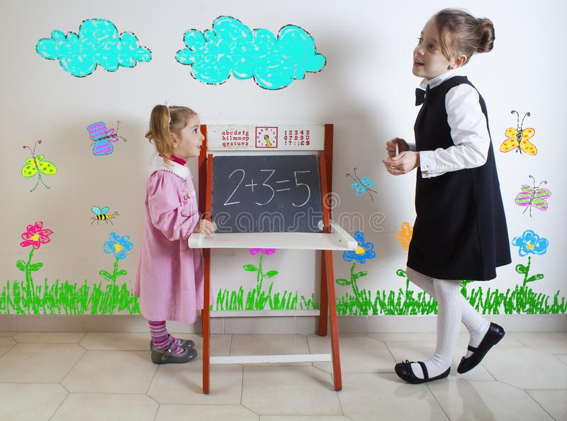Little girl teaching mathematics to a younger child stock image