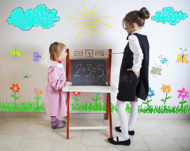 Little girl teaching mathematics to a younger child stock photography