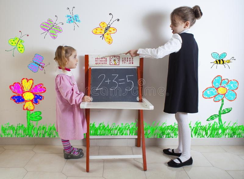 Little girl teaching mathematics to a younger child royalty free stock photography
