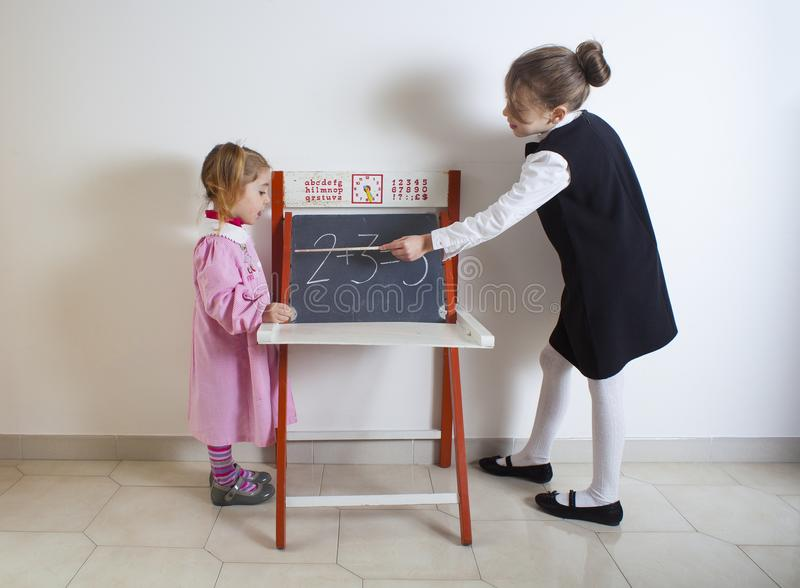 Little girl teaching mathematics to a younger child stock photo