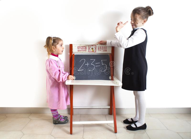 Little girl teaching mathematics to a younger child royalty free stock photo