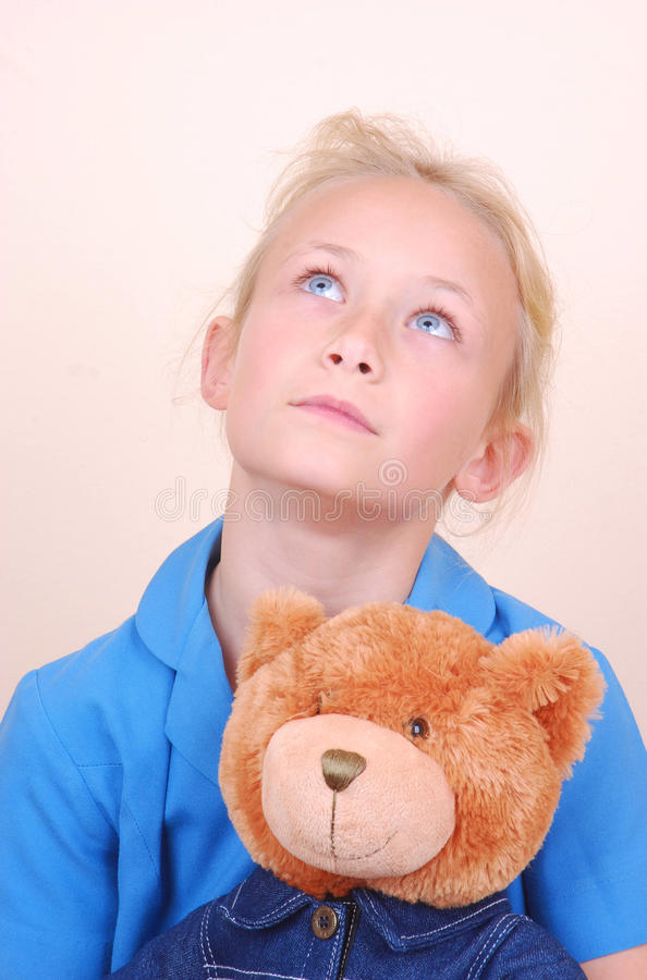 Little girl with teddy bear. Portrait of a beautiful little sad Caucasian girl with her cute soft teddy bear looking up to heaven stock photos