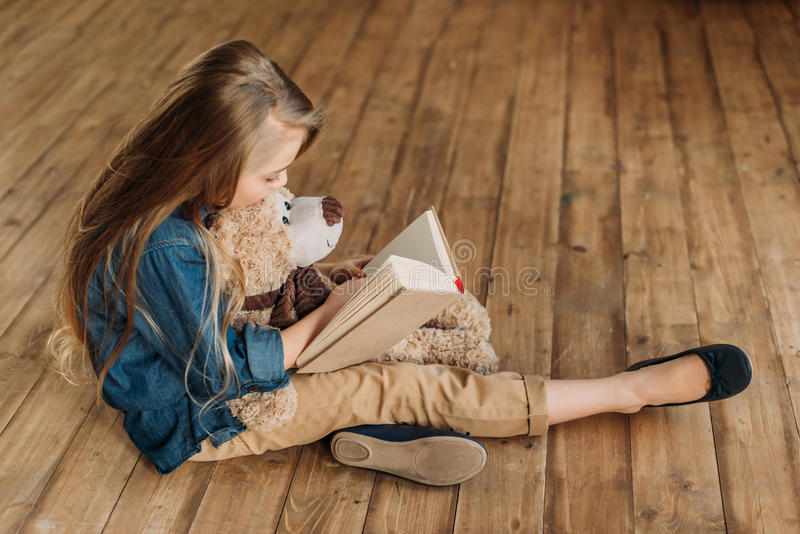 Little girl with teddy bear reading book, education kids concept royalty free stock image