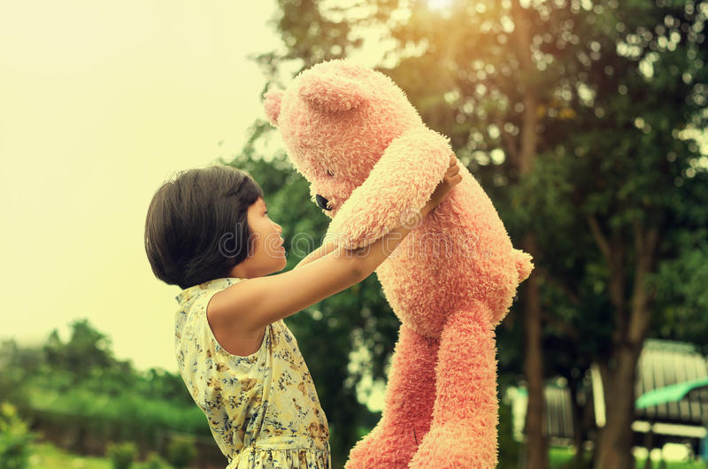 Little girl with teddy bear standing and sunset. At park stock photo