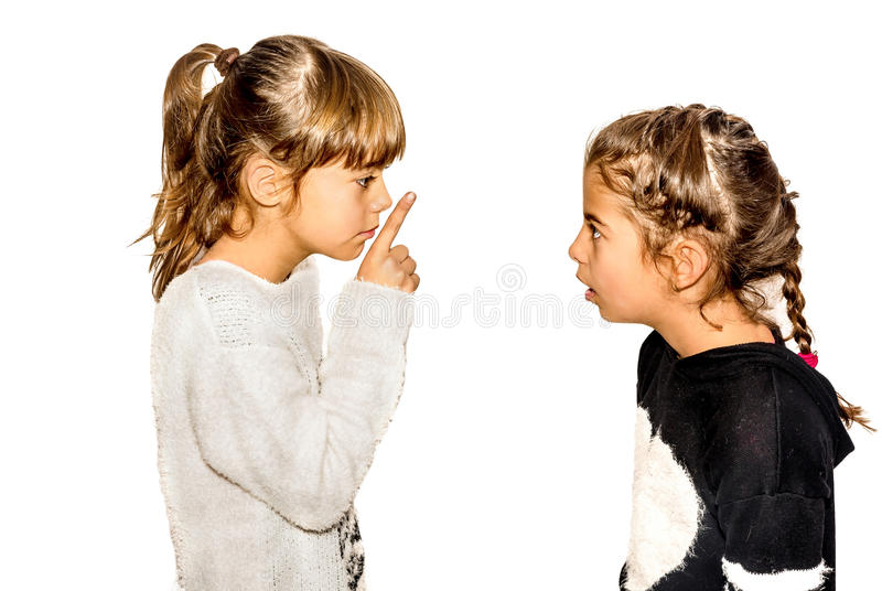Little girl telling her sister to shut up with her finger on the. Mouth. A gesture of silence . Closeup-Isolated on white background royalty free stock photos