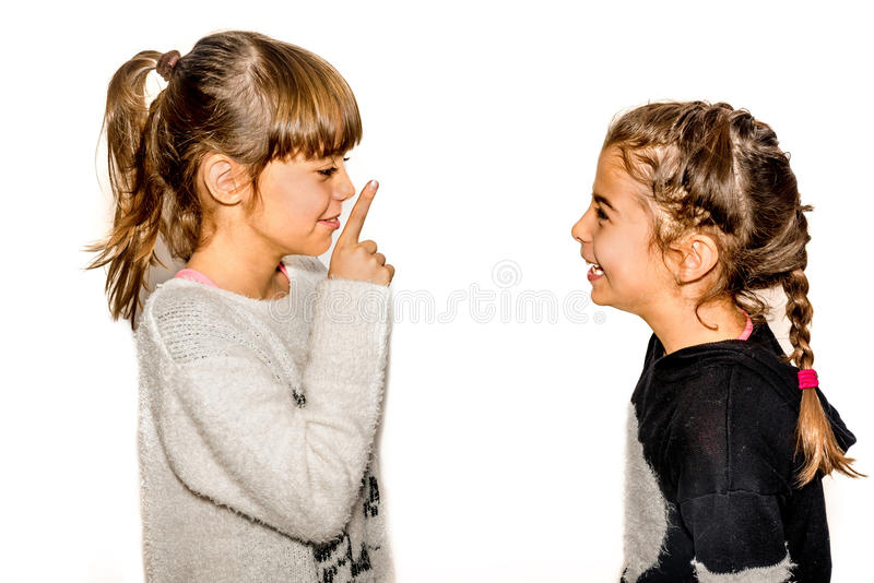 Little girl telling her sister to shut up with her finger on the. Mouth. A gesture of silence . Closeup-Isolated on white background stock image
