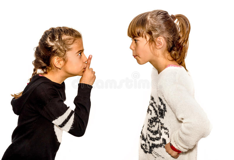 Little girl telling her sister to shut up with her finger on the. Mouth. A gesture of silence . Closeup-Isolated on white background royalty free stock image
