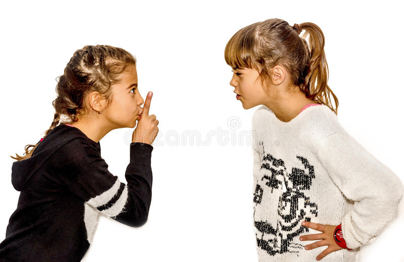 Little girl telling her sister to shut up with her finger on the. Mouth. A gesture of silence . Closeup-Isolated on white background royalty free stock images