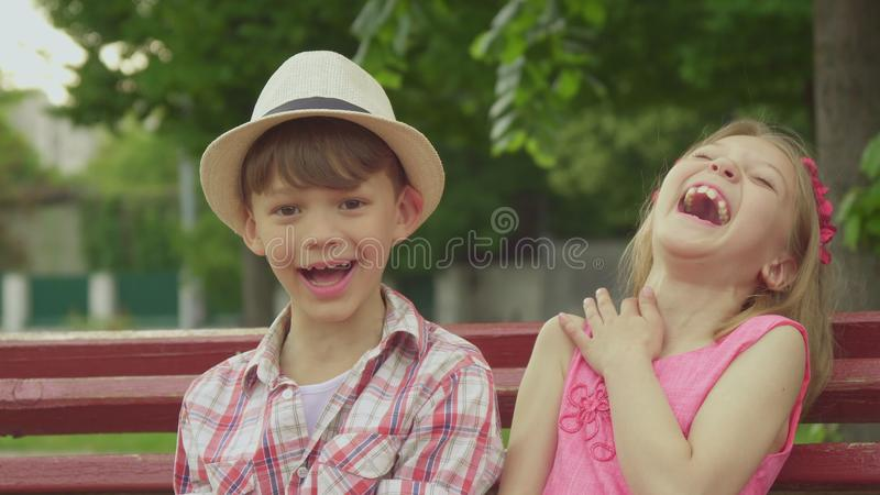 Little girl tells something to the boy on the bench stock photography