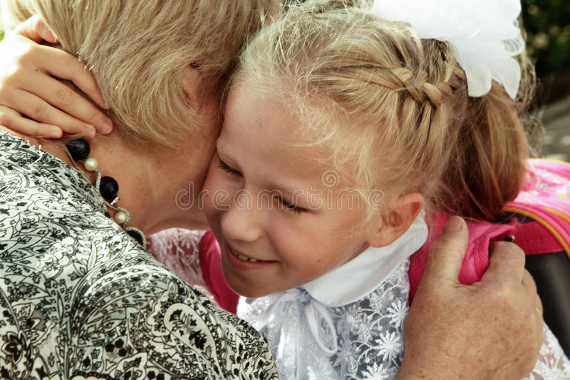 Little girl tenderly embraces grandmother in day back to school stock image