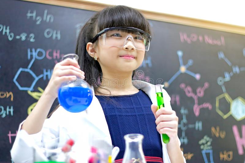 Little girl with test tube making experiment at school laboratory. Science and education stock photo