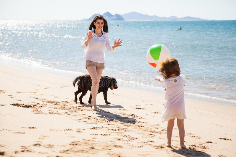 Little girl throwing the ball. Beautiful Hispanic single mom having fun and playing with a ball with her daughter and dog at the beach royalty free stock photos