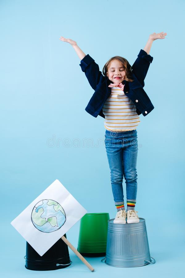 Little girl throwing hands in air. Standing on bucket next to planet earth sign stock photography