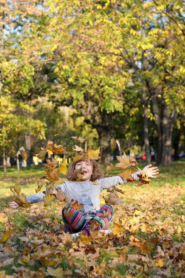 Download Little Girl Throws Autumn Leaves Stock Photo - Image: 27563054