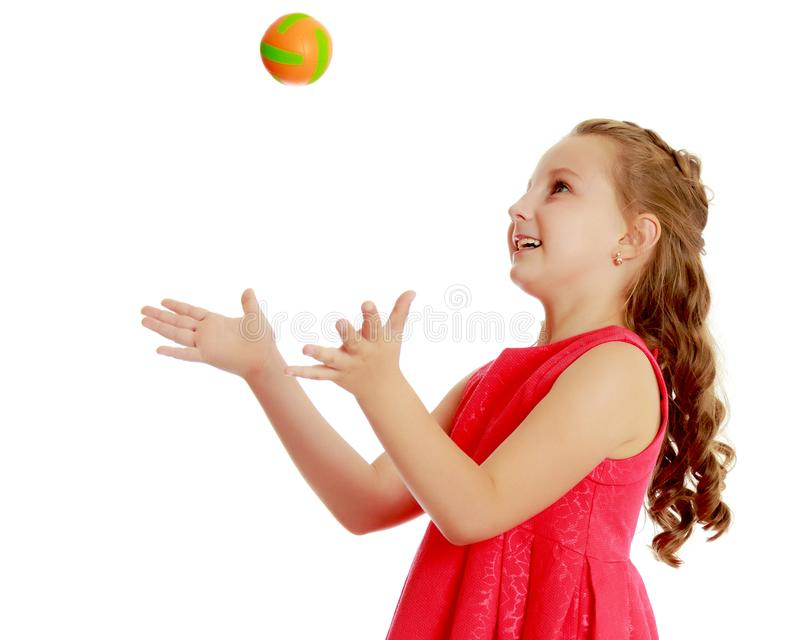 The little girl throws the ball up stock photography