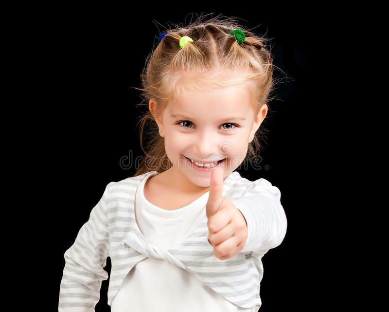 Little girl with thumbs up. On black background royalty free stock photography