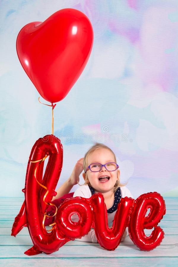 Little girl toddler with red heart balloonand love sign. Valentines day concept royalty free stock photos