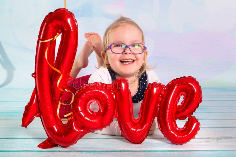 Little girl toddler with red heart balloonand love sign. Valentines day concept stock photography