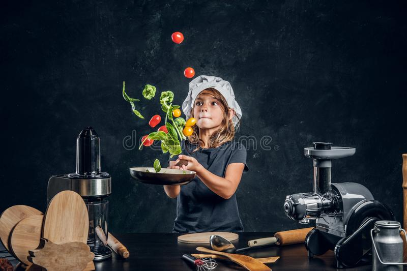 Little girl is tossing vegetables on the pan royalty free stock photo
