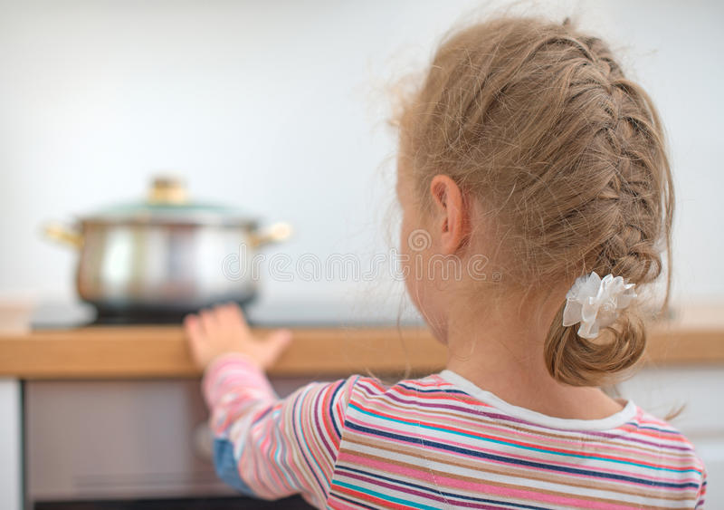 Little girl touches hot pan on the stove. Dangerous situation at home royalty free stock images