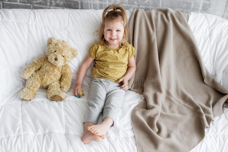 A little girl and a toy bear royalty free stock photos
