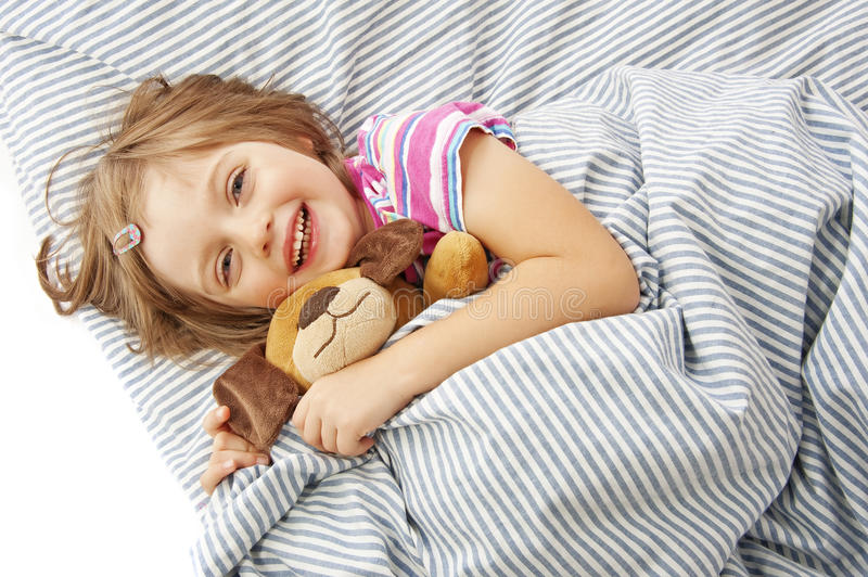 Little girl with toy in the bed stock photo