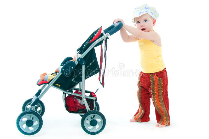 The little girl with a toy carriage stock photography