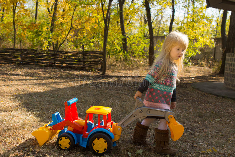 Little girl with a toy construction vehicle. Little girl playing with a colorful vivid plastic toy construction vehicle outdoors in the park in the autumn stock images