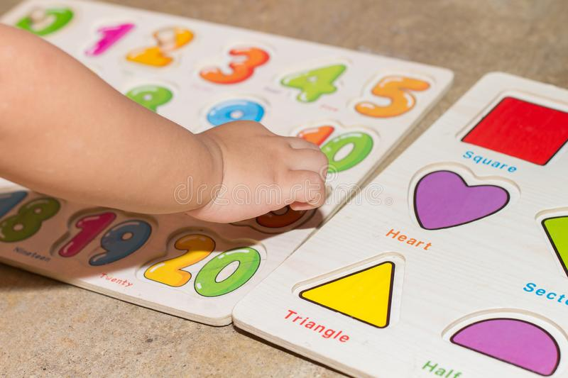 Little girl with toy numbers educational games at home, Board games for children modern learning,Girl learning counting number toy. Colored numbers math royalty free stock photography