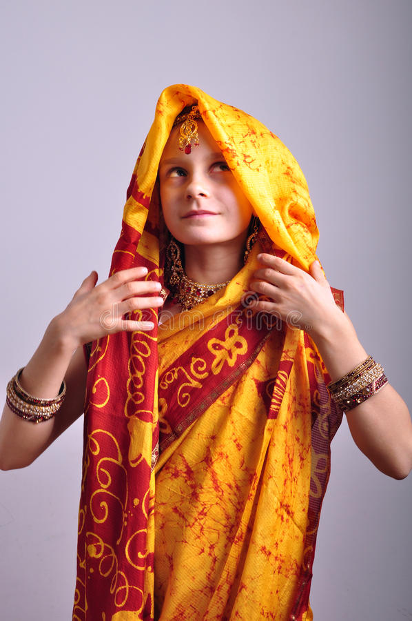 Little girl in traditional Indian clothing and jeweleries. Portrait of a little girl in traditional Indian clothing, sari and jeweleries royalty free stock image