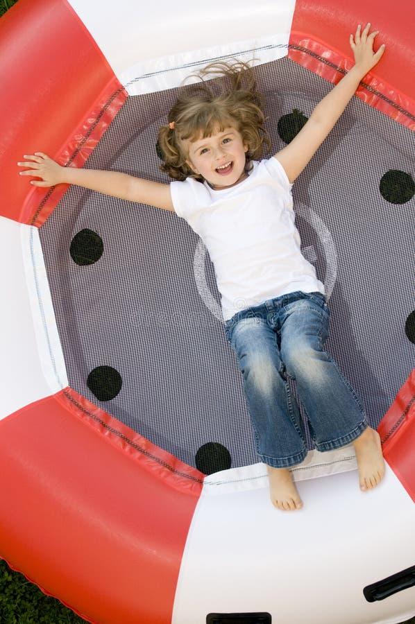 Little girl on trampoline stock photography