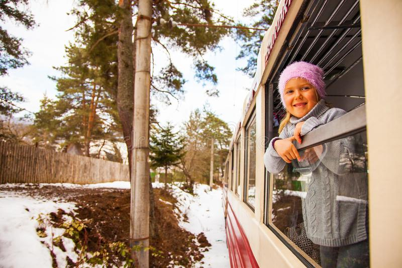 Little girl travelling by Kukushka old train in Georgia stock photo