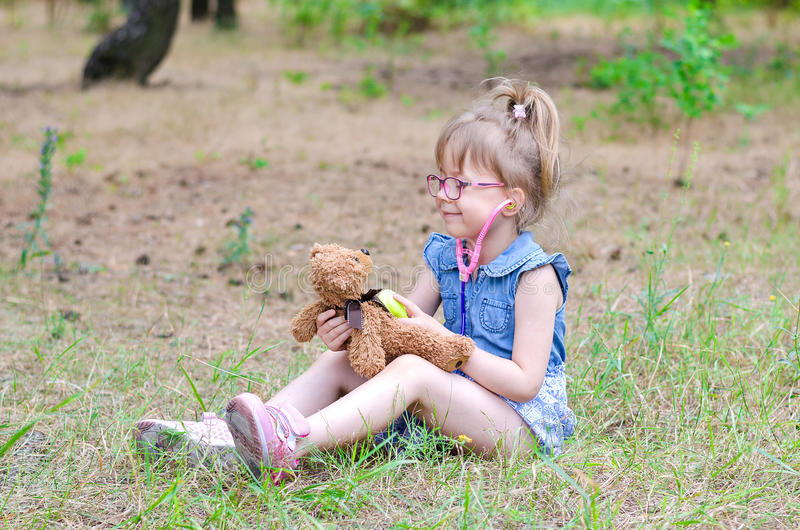 A little girl treats her teddy bear in a forest glade a copy of stock photos