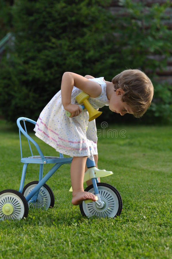 Little girl on the tricycle royalty free stock photos