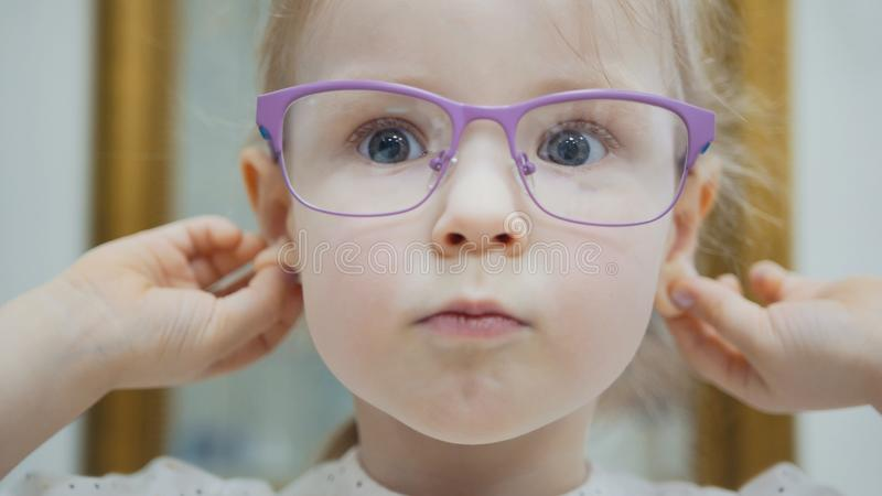 Little girl tries fashion medical glasses near mirror - shopping in ophthalmology clinic. Close up stock images